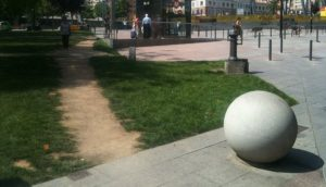 A stone walkway into a larger plaza is partially obstructed by a large stone sphere; walkers have worn their own path around it in the nearby grass.